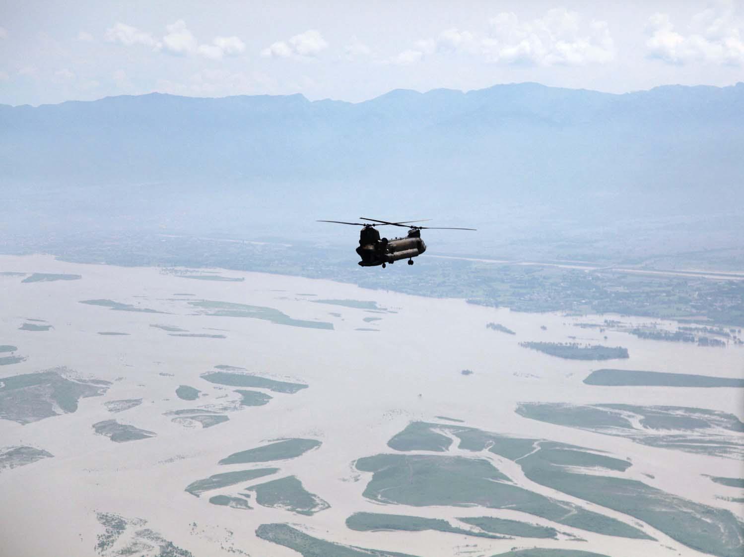 Helikopter fliegt über ein von Überschwemmungen betroffenes Gebiet in Pakistan
