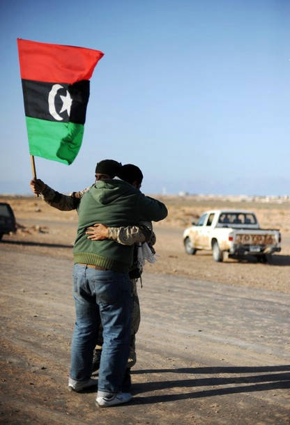 A Libyan rebel holding the old national flag embraces with fellow fighter on March 7, 2011 in Ras Lanuf as opposition forces ceded ground to Moamer Kadhafi's advancing forces, and the United States came under increasing pressure to arm the opposition and the UN appointed a humanitarian envoy.       AFP PHOTO/ROBERTO SCHMIDT (Photo credit should read ROBERTO SCHMIDT/AFP/Getty Images)    Bild: © BRQ Network [CC BY 2.0]  - Flickr