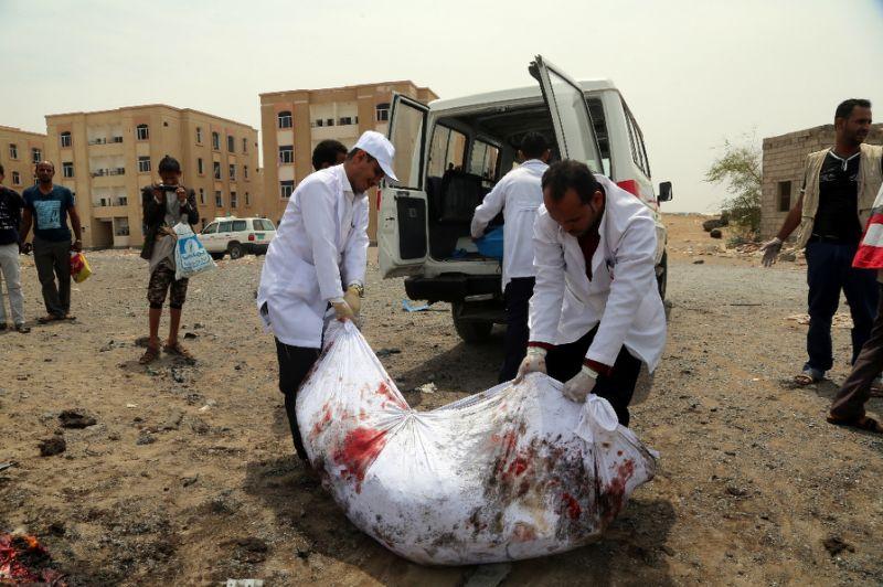 Zwei Männer tragen einen Leichensack in den LKW.